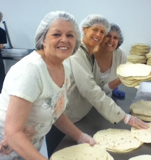 Smiling and sorting tortillas for 2nd Harvest Heartland